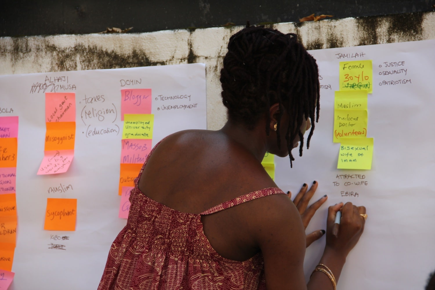 A woman writing on a whiteboard with sticky notes at a Book Sprint in Nigeria